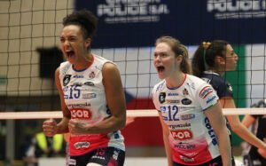 Two women's volleyball players cheer for their teamamtes