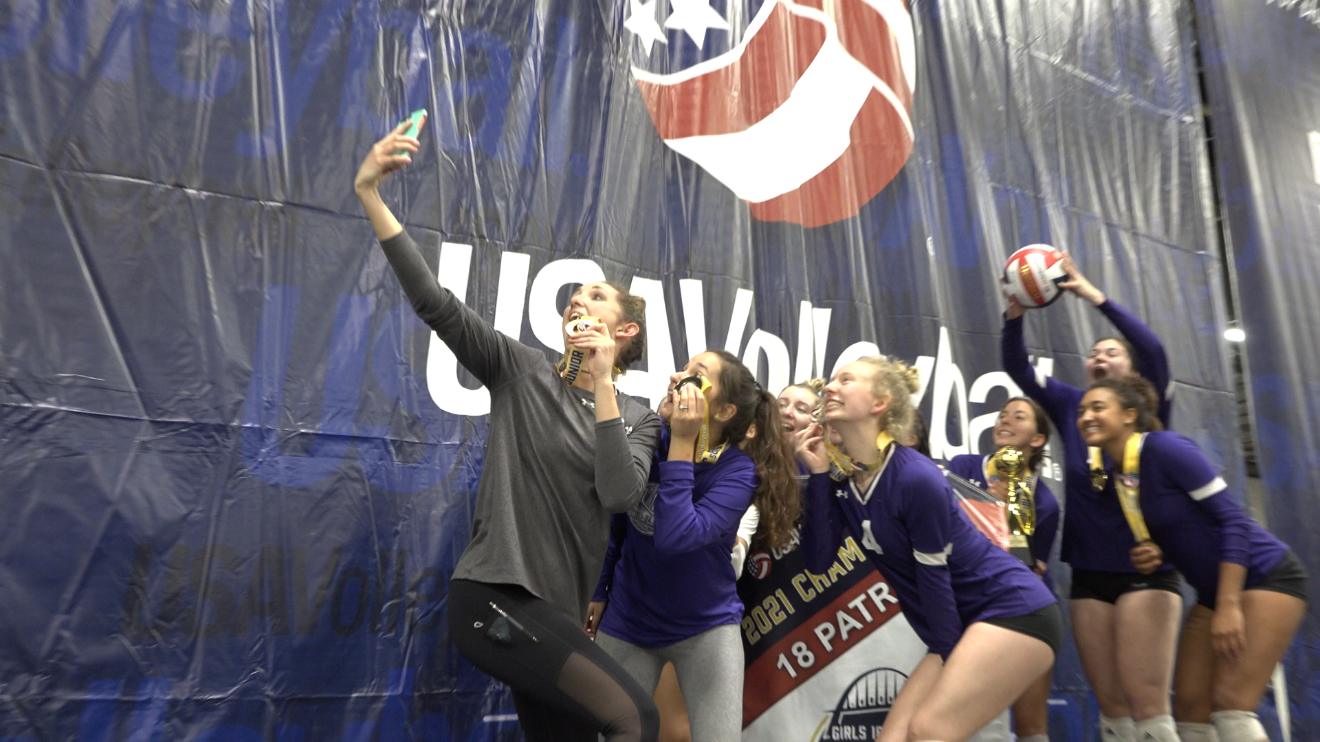 Hallie Enderle and her team (NIVA 18X) celebrate with a selfie on the championship stage at GJNC 18s.