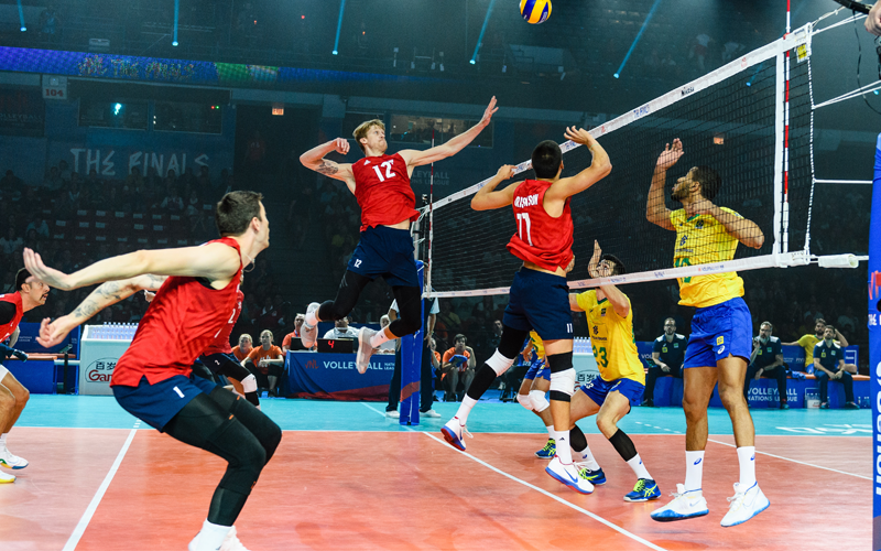 U.S. Men's National Team middle Max Holt getting ready to attack a ball set to him from teammate Micah Christenson versus Brazil at the 2019 Volleyball Nations League tournament.
