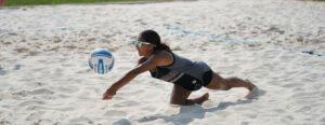 girl digging ball on beach