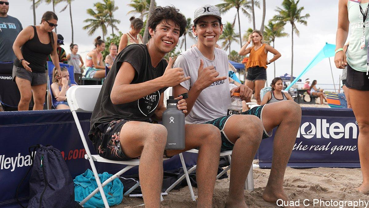 Boys giving hang loose sign at beach tournament